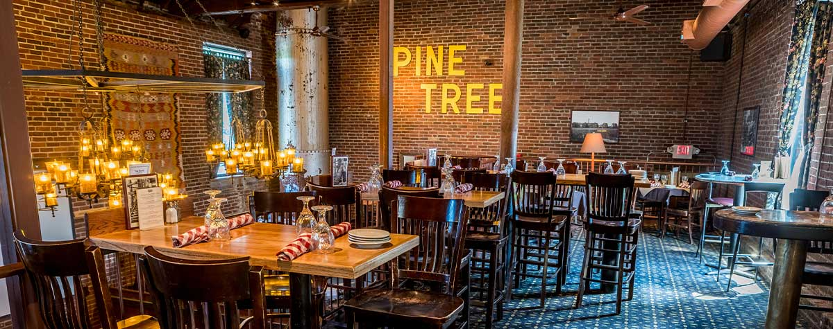 "dining room with high top tables upstairs of fosters boiler room brick walls and ""pine tree"" lettered sign on back waller"