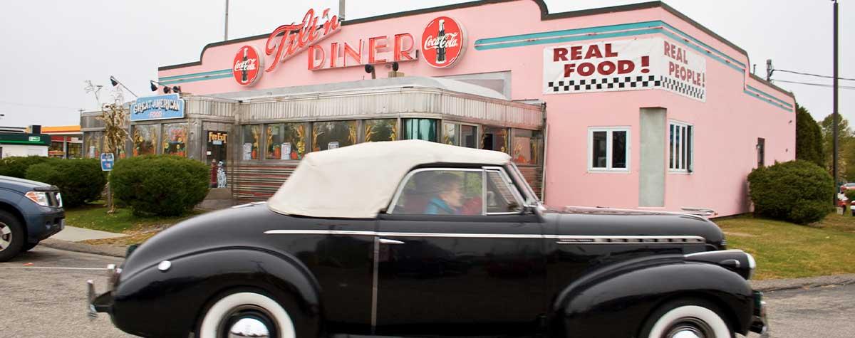 black classic car in front of tilt'n diner