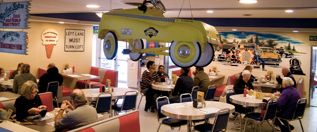 wider image of dining room, people dining, classic car decor hangs from ceiling