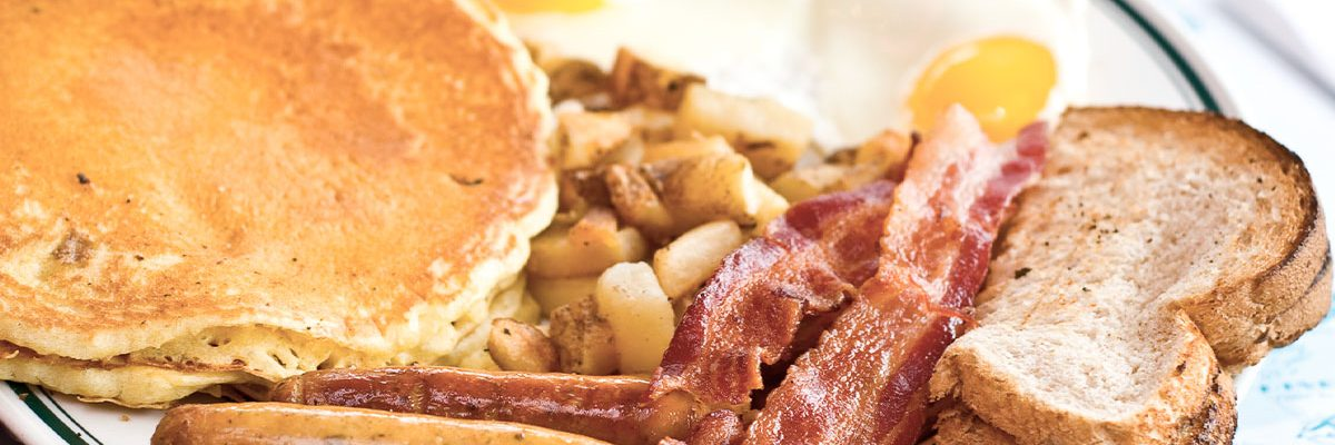 pancakes, sausage, bacon, toast and sunnyside up eggs breakfast platter