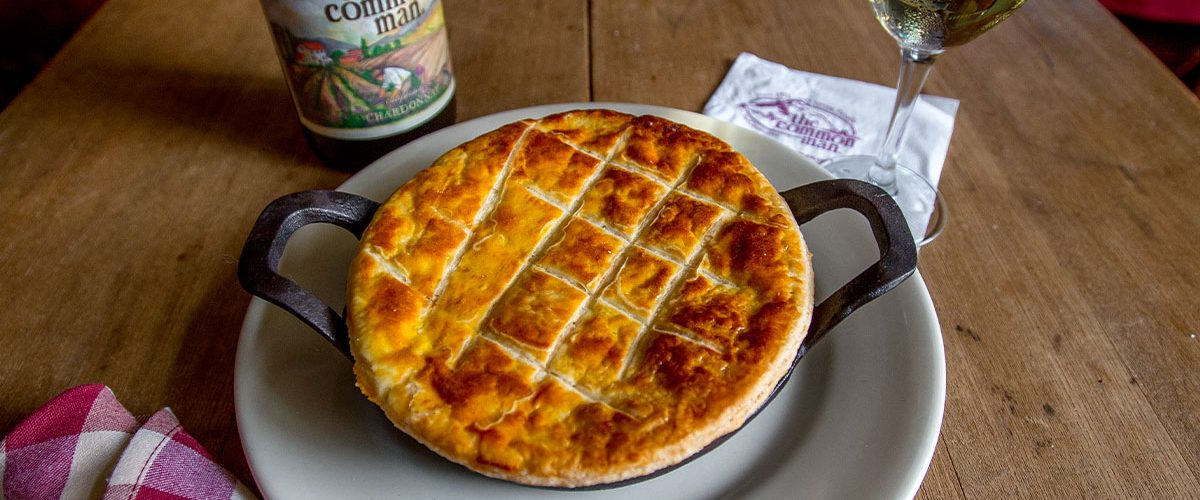 chicken pot pie in skillet on plate with common man wine bottle and full glass