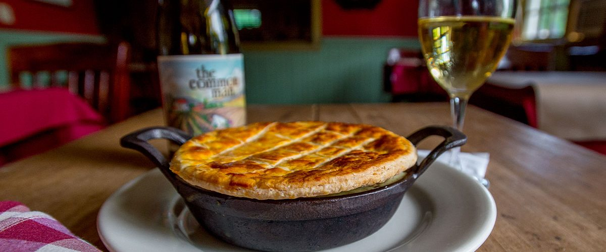 chicken pot pie in skillet on plate with common man wine and full wine glass in background