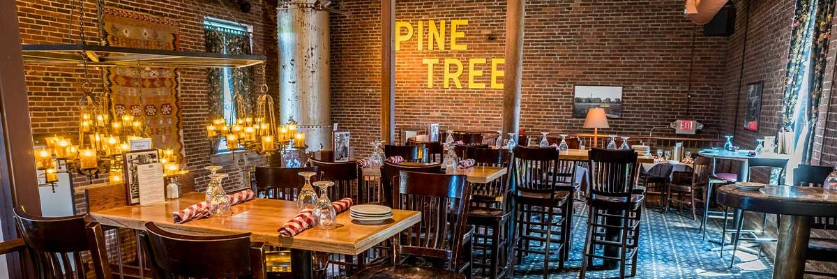 dining room with high top tables upstairs of fosters boiler room brick walls and