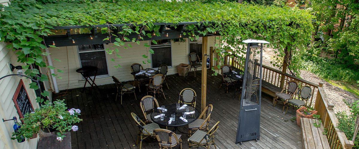 italian farmhouse arbor covering tables on outside patio