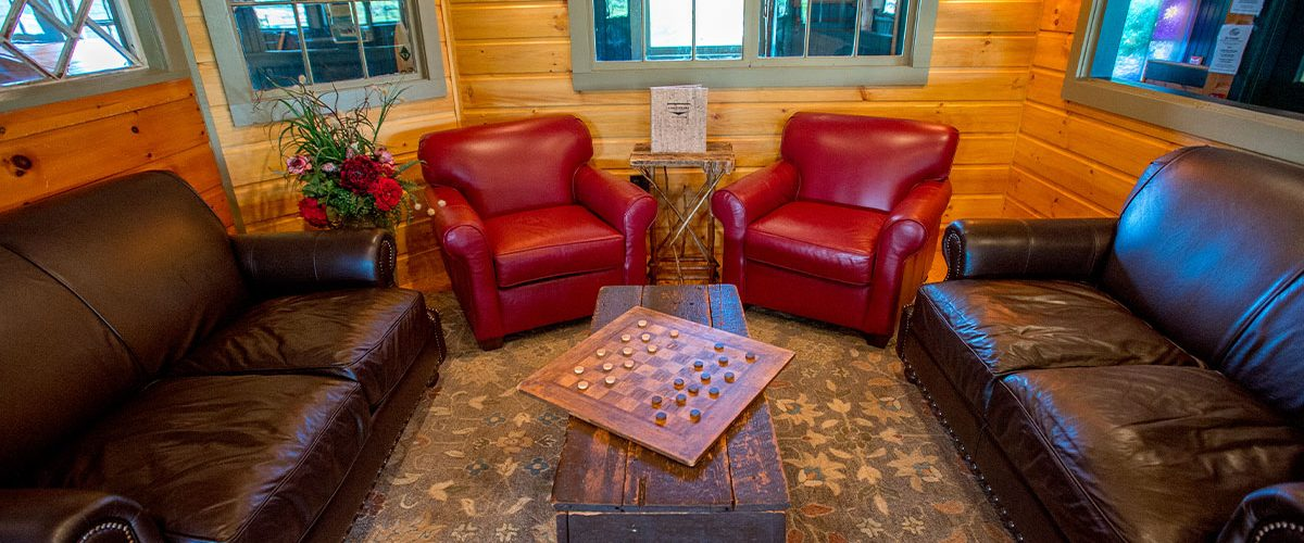 leather lounge chairs and sofa with checkers set up