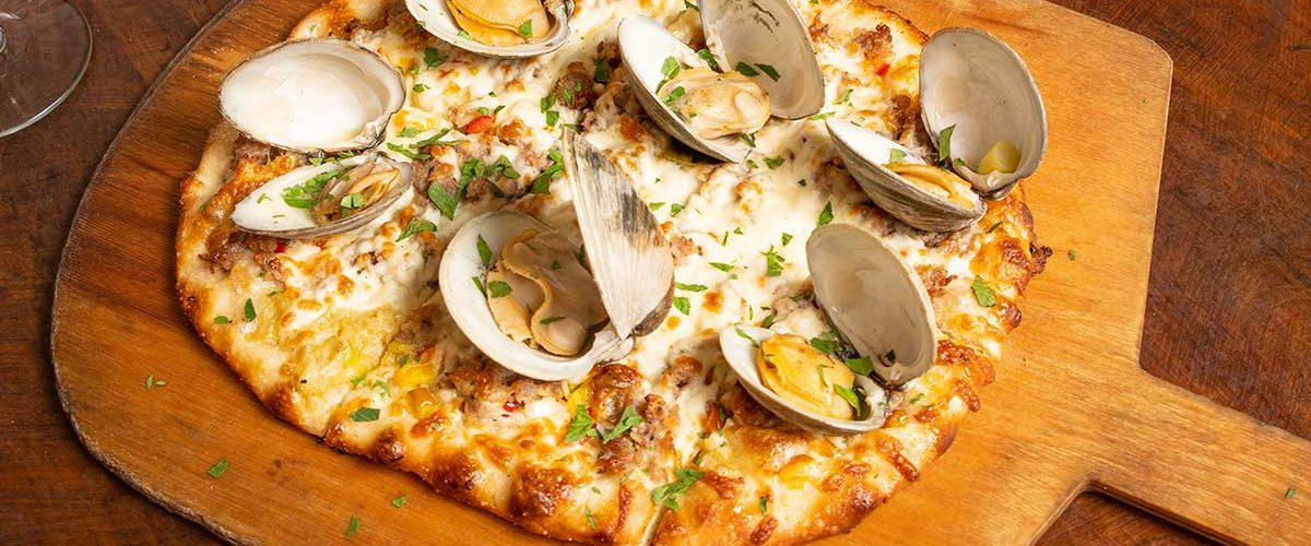 clam pizza on wooden board