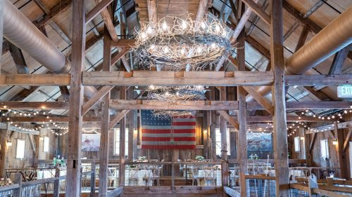 second floor of barn tables around in half circle around balcony opening to first floor with chandeliers lit from wood beamed ceiling
