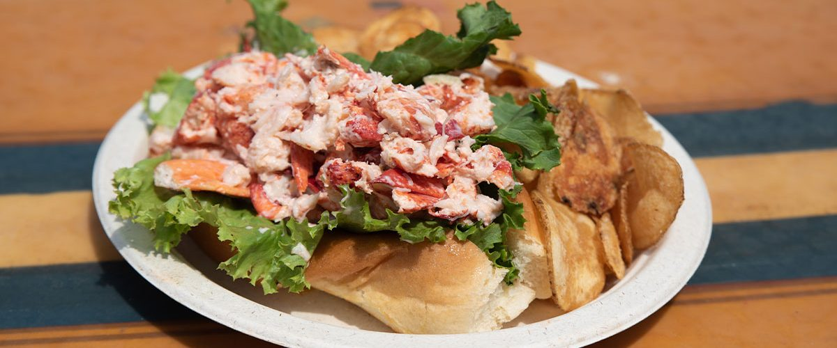 lobster roll on a plate with chips